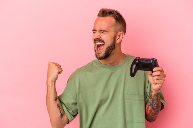 Junger kaukasischer mann mit tätowierungen, der einen gamecontroller einzeln auf rosafarbenem hintergrund hält und nach einem sieg die faust anhebt, gewinnerkonzept.