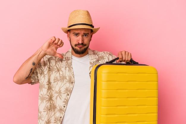 Junger kaukasischer mann mit tätowierungen, der einzeln auf rosafarbenem hintergrund reisen wird, fühlt sich stolz und selbstbewusst, beispiel zu folgen.