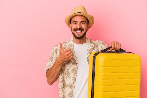 Junger kaukasischer mann mit tätowierungen, der isoliert auf rosafarbenem hintergrund reisen wird, lächelt und hebt den daumen hoch