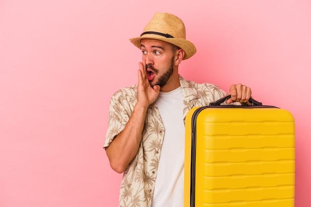 Junger kaukasischer mann mit tätowierungen, der isoliert auf rosafarbenem hintergrund reisen wird, sagt eine geheime heiße bremsnachricht und schaut beiseite