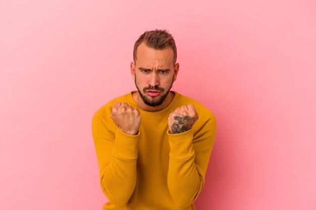 Junger kaukasischer mann mit tätowierungen, die auf rosafarbenem hintergrund isoliert sind, verärgert schreiend mit angespannten händen.