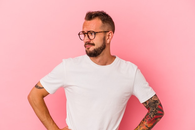 Junger kaukasischer mann mit tätowierungen, die auf rosafarbenem hintergrund isoliert sind, verwirrt, fühlt sich zweifelhaft und unsicher.