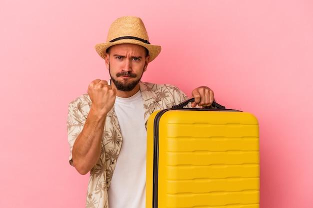 Junger kaukasischer mann mit tätowierungen, die einzeln auf rosafarbenem hintergrund reisen, der die faust zur kamera zeigt, aggressiver gesichtsausdruck.