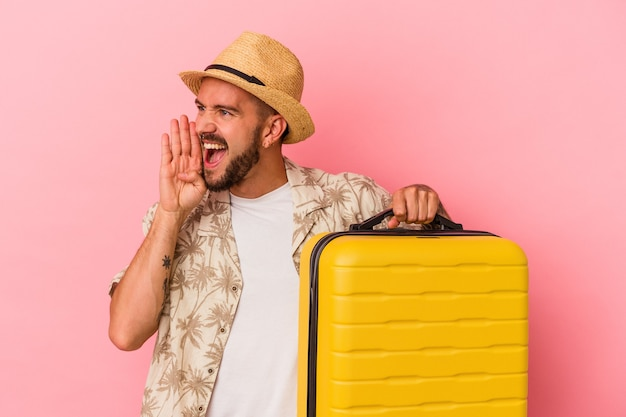 Junger kaukasischer mann mit tätowierungen, die einzeln auf rosafarbenem hintergrund reisen, schreien und die handfläche in der nähe des geöffneten mundes halten.