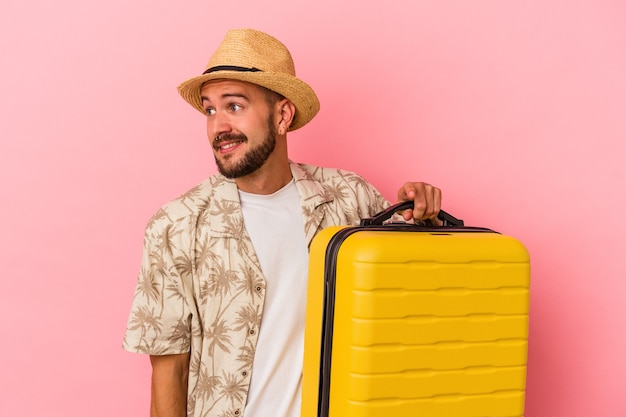 Junger kaukasischer mann mit tätowierungen, die einzeln auf rosafarbenem hintergrund reisen, sieht beiseite lächelnd, fröhlich und angenehm aus.