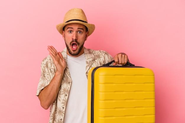 Junger kaukasischer mann mit tätowierungen, die einzeln auf rosafarbenem hintergrund reisen, überrascht und schockiert.