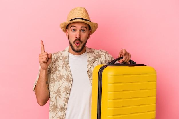 Junger kaukasischer mann mit tätowierungen, die einzeln auf rosafarbenem hintergrund reisen und eine großartige idee haben, konzept der kreativität.