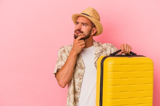 Junger kaukasischer mann mit tätowierungen, die einzeln auf rosafarbenem hintergrund reisen und seitlich mit zweifelhaftem und skeptischem ausdruck schauen.