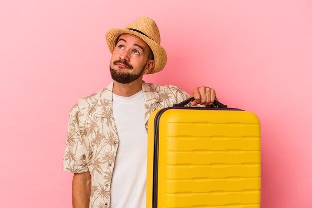 Junger kaukasischer mann mit tätowierungen, die isoliert auf rosafarbenem hintergrund reisen und davon träumen, ziele und zwecke zu erreichen