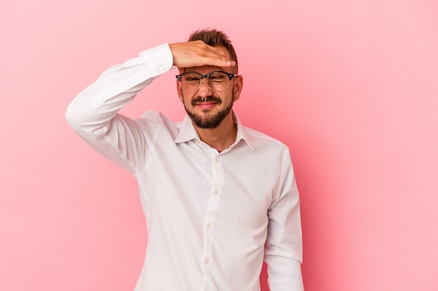 Junger kaukasischer mann mit tätowierungen einzeln auf rosafarbenem hintergrund, die tempel berühren und kopfschmerzen haben.