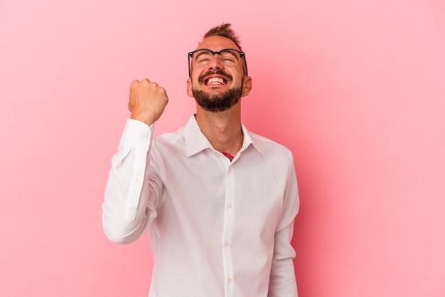 Junger kaukasischer mann mit tätowierungen einzeln auf rosafarbenem hintergrund feiert sieg, leidenschaft und begeisterung, glücklichen ausdruck.