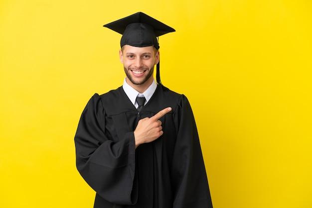 Junger kaukasischer mann mit universitätsabschluss isoliert auf gelbem hintergrund, der auf die seite zeigt, um ein produkt zu präsentieren