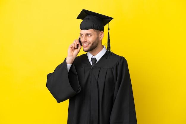 Junger kaukasischer mann mit universitätsabschluss isoliert auf gelbem hintergrund, der ein gespräch mit dem mobiltelefon mit jemandem führt