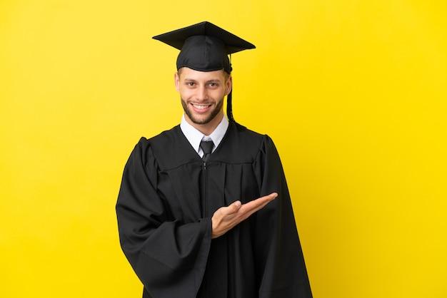 Junger kaukasischer mann mit universitätsabschluss isoliert auf gelbem hintergrund, der eine idee präsentiert, während er lächelnd in richtung blickt