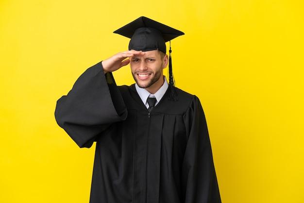 Junger kaukasischer mann mit universitätsabschluss isoliert auf gelbem hintergrund, der mit der hand weit weg schaut, um etwas zu suchen