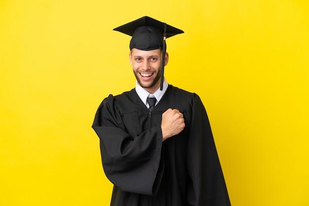 Junger kaukasischer mann mit universitätsabsolvent isoliert auf gelbem hintergrund, der einen sieg feiert
