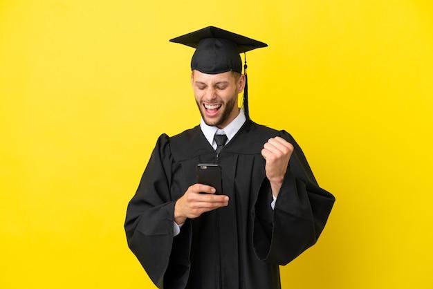 Junger kaukasischer mann mit universitätsabsolvent isoliert auf gelbem hintergrund mit telefon in siegesposition