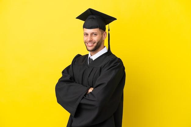 Junger kaukasischer mann mit universitätsabsolvent isoliert auf gelbem hintergrund mit verschränkten armen und freut sich