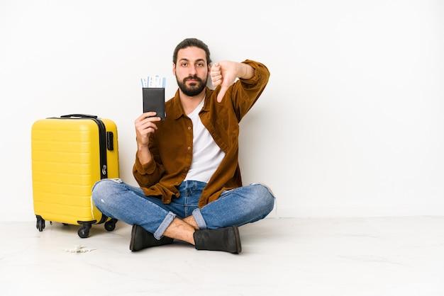 Junger kaukasischer mann sitzend, der einen pass und einen koffer isoliert hält und eine abneigungsgeste zeigt, daumen nach unten. uneinigkeit konzept.