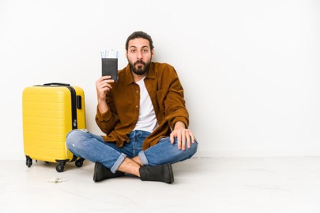 Junger kaukasischer mann sitzend, der einen pass und einen koffer isoliert hält, zuckt mit den schultern und die offenen augen verwirrt.
