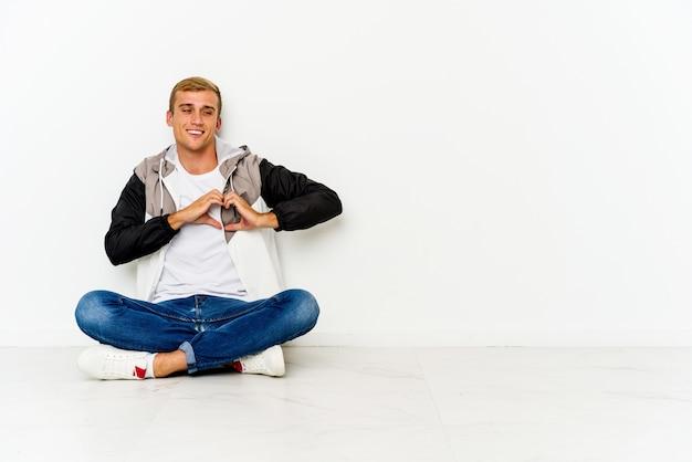 Junger kaukasischer mann sitzt auf dem boden lächelnd und zeigt eine herzform mit händen.