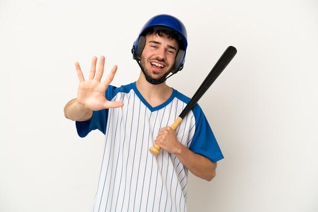 Junger kaukasischer mann spielt baseball isoliert auf weißem hintergrund und zählt fünf mit den fingern