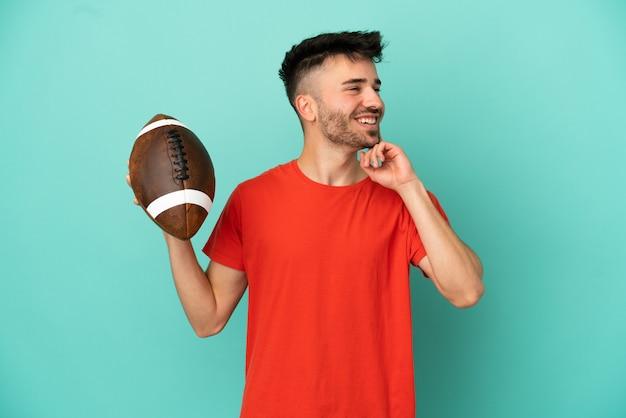 Junger kaukasischer mann spielt rugby isoliert auf blauem hintergrund und denkt beim nachschlagen eine idee