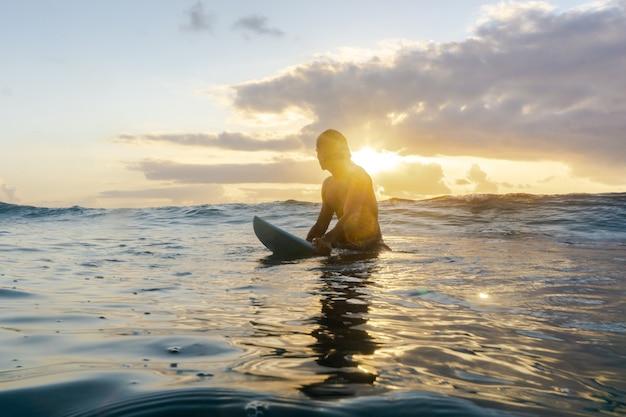 Junger kaukasischer mann steht früh auf, um bei sonnenaufgang zu surfen