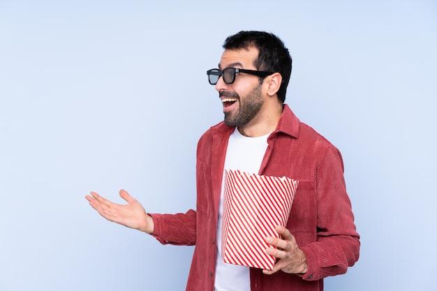 Junger kaukasischer mann über blauer wand mit gläsern 3d und dem halten eines großen eimers popcorns