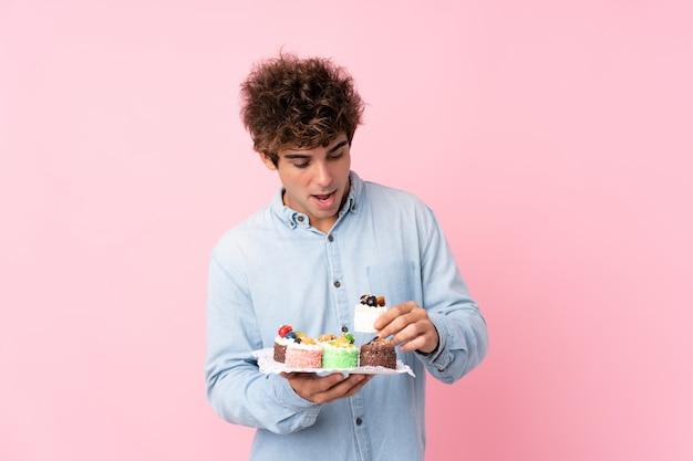 Junger kaukasischer mann über dem lokalisierten rosa, das minikuchen hält und überrascht