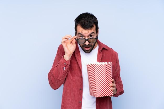 Junger kaukasischer mann über der blauen wand überrascht mit gläsern 3d und einem großen eimer popcorn halten