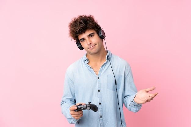 Junger kaukasischer mann über der lokalisierten rosa wand, die an den videospielen spielt