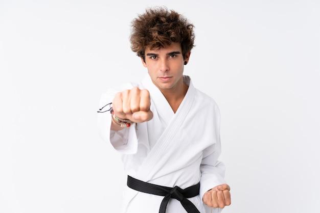 Junger kaukasischer mann über der lokalisierten weißen wand, die karate tut