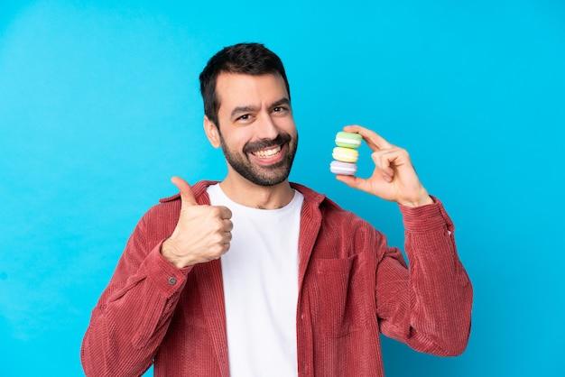 Junger kaukasischer mann über isoliertem blau, das bunte französische macarons mit daumen oben hält