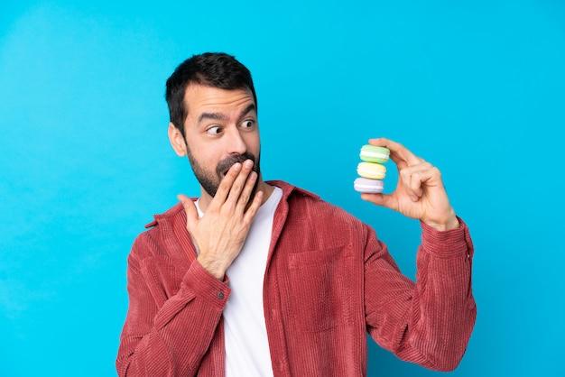 Junger kaukasischer mann über isolierter blauer wand, die bunte französische macarons und mit überraschungsausdruck hält