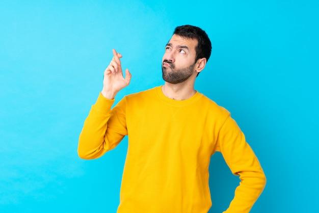 Junger kaukasischer mann über isolierter blauer wand mit den fingern kreuzend und wünschend das beste