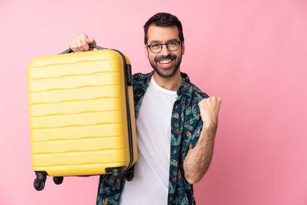 Junger kaukasischer mann über isolierter wand im urlaub mit reisekoffer