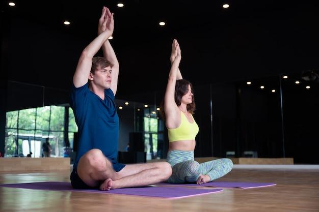 Junger kaukasischer mann und frau im yogaklassenraum-eignungstraining
