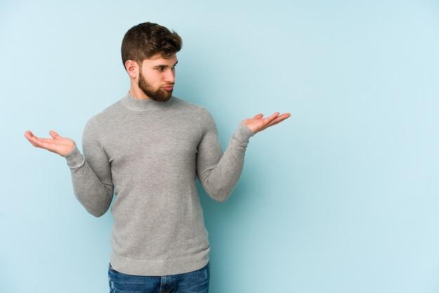 Junger kaukasischer mann verwirrt und zweifelhaft mit den schultern zuckend, um einen kopierraum zu halten.