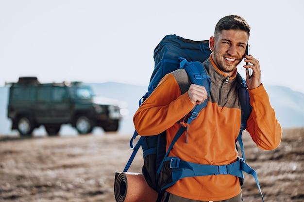 Junger kaukasischer mannreisender, der sein smartphone benutzt