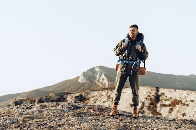 Junger kaukasischer mannreisender mit dem großen rucksack, der in den bergen wandert