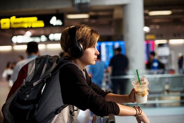 Junger kaukasischer reisender, der getränkgetränk im flughafen hält