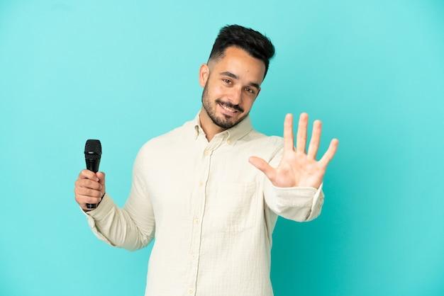 Junger kaukasischer sänger mann isoliert auf blauem hintergrund, der fünf mit den fingern zählt