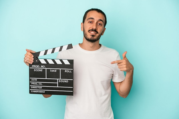 Junger kaukasischer schauspieler, der eine klappe isoliert auf blauem hintergrund hält, die mit der hand auf einen hemdkopierraum zeigt, stolz und selbstbewusst