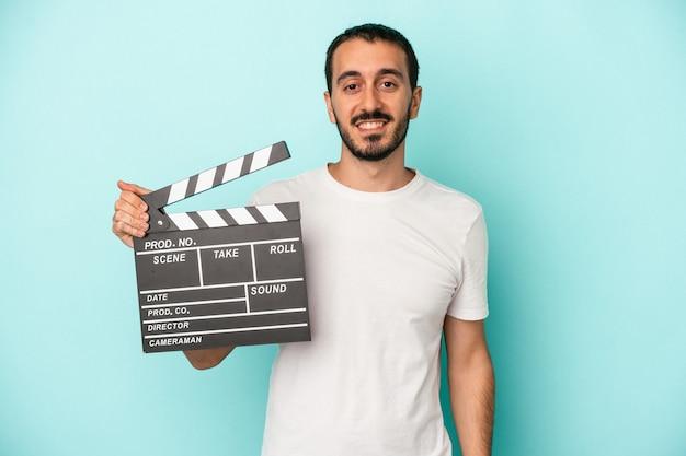 Junger kaukasischer schauspielermann, der clapperboard lokalisiert auf blauem hintergrund glücklich, lächelnd und fröhlich hält.