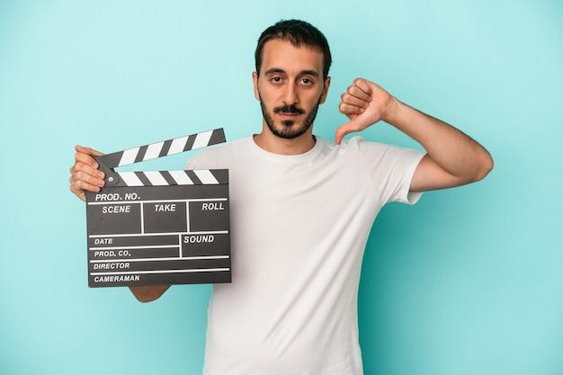 Junger kaukasischer schauspielermann, der clapperboard lokalisiert auf blauem hintergrund hält, der eine abneigungsgeste zeigt, daumen nach unten. meinungsverschiedenheit konzept.