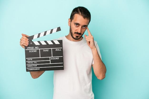 Junger kaukasischer schauspielermann, der clapperboard lokalisiert auf blauem hintergrund hält, der mit dem finger auf den tempel zeigt und denkt, konzentriert sich auf eine aufgabe.