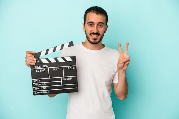 Junger kaukasischer schauspielermann, der clapperboard lokalisiert auf blauem hintergrund hält, der nummer zwei mit den fingern zeigt.