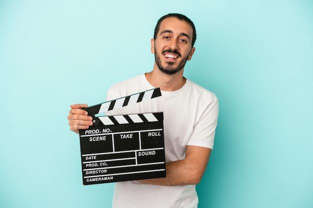 Junger kaukasischer schauspielermann, der clapperboard lokalisiert auf blauem hintergrund hält, lacht und spaß hat.