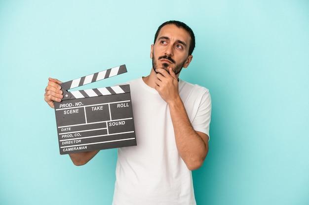Junger kaukasischer schauspielermann, der clapperboard lokalisiert auf blauem hintergrund hält und seitlich mit zweifelhaftem und skeptischem ausdruck schaut.